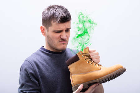 Close-up Of A Young Man Holding Stinky Shoes Against White Background