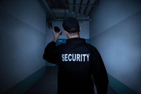 Rückansicht eines männlichen Wachmanns mit Taschenlampe im Korridor