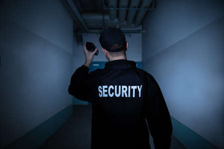 Rear View Of A Male Security Guard With Flashlight Standing In Corridor