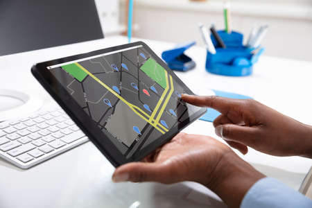 Close-up Of A Woman's Hand Using GPS Navigation Map On Digital Tablet Over The Desk