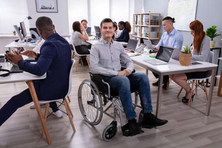Portrait Of A Disabled Businessman On Wheelchair At Office Stock Photo