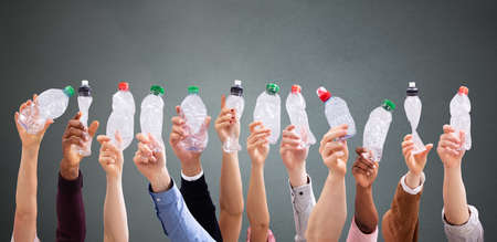 Group Of People's Hand Holding Crushed Water Bottles Against Dark  Background Standard-Bild