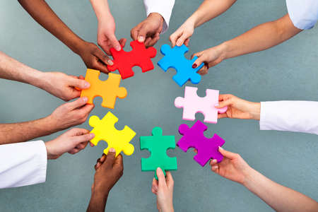 High Angle View Of Medical Team Solving Colorful Jigsaw Puzzle Against Grey Background