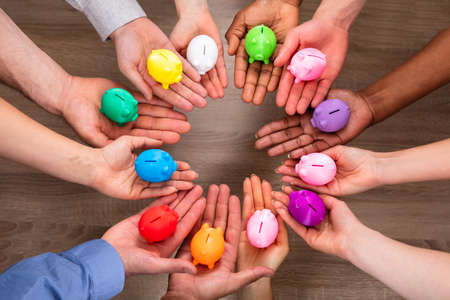 Elevated View Of People's Hand Holding Colorful Piggybanks Over Wooden Desk