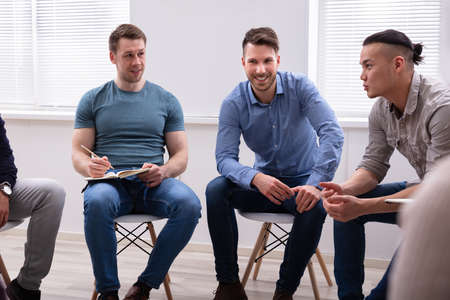 Smiling Men Looking At Their Male Friend While Discussion