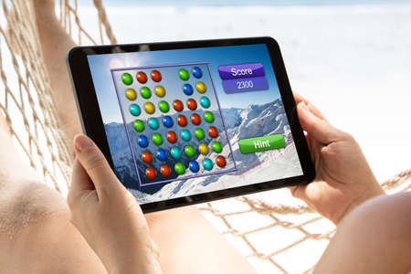 Close-up Of A Woman Lying On Hammock Playing Video Game On Digital Tablet At Beach