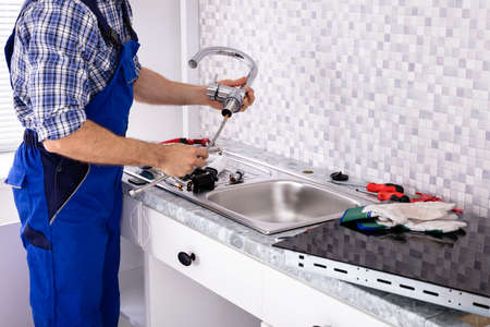 Mid Section Of Male Plumber Assembling The Kitchen Sink Faucet Stockfoto
