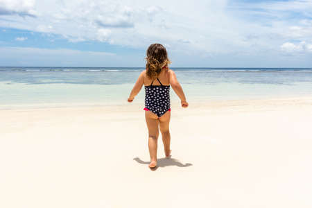 Little Girl In Bikini Walking On The Idyllic Anse Baleine Beach, Mahe Island, Seychelles 스톡 콘텐츠