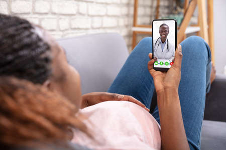 Close-up Of Pregnant Woman Video Calling Her Doctor On Mobilephone