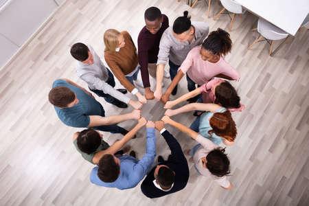 Ein Blick von oben auf die Hand multiethnischer Menschen, die ihre Faust zu einem Kreis vereinigen Standard-Bild