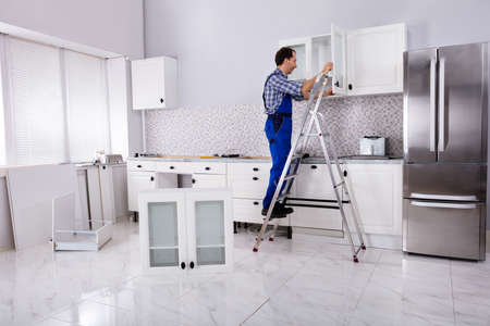 Rear View Of A Male Carpenter Assembling White Cabinet On Wall In Kitchen