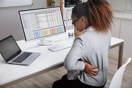 Side View Of African Businesswoman Holding Her Back While Working On Laptop At Office Desk Stockfoto