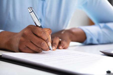 Close-up de la mano de una empresaria llenando el formulario de contrato