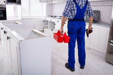 Rear View Of A Repairman In Uniform Holding Tool Box Installing Kitchen Induction Ceramic Hob