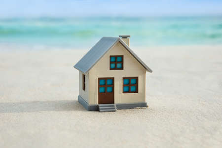 Miniature House Model On The Idyllic Beach Near The Coast 스톡 콘텐츠