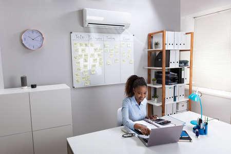 Glimlachende zakenvrouw genieten van de koeling van de airconditioner met behulp van Laptop op de werkplek