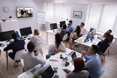 Rear View Of A Business People Looking At Screen During Video Conference In Office