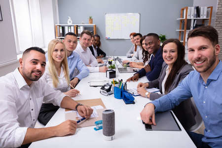 Group Of Multiethnic Diverse Busy Business People Sitting Together At Table In The Office Stockfoto