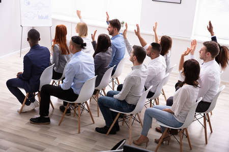 Multi Ethnic Business People Sitting On Chair In Row Raising Their Arms In The Office