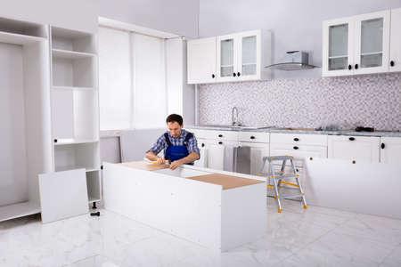Carpenter Repair And Assembling Furniture In The Modular Kitchen Stockfoto - 124789736