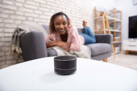 Woman Using Voice Assistant Speaker On Table