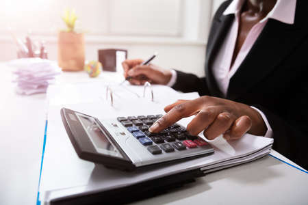 Photo Of Businesswoman's Hand Calculating Bill In Office