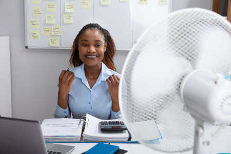 Young Businesswoman Sitting In Office Enjoying Breeze With Electric Fan