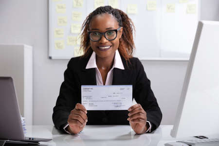 Close-up Of A Smiling Businesswoman Showing Company Cheque Stock Photo