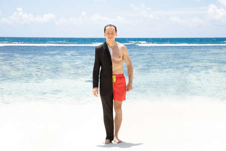 Portrait Of A Man In Formalwear And Shorts Standing In Front Of Sea At Beach