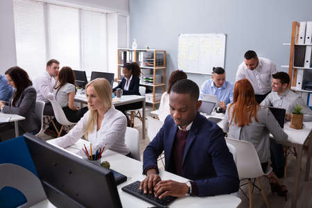 Group Of Multi-ethnic Businesspeople Working On Computer In Office