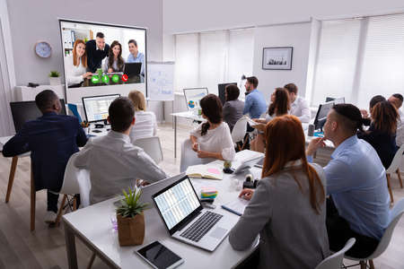 Rear View Of A Business People Looking At Screen During Video Conference In Office Stockfoto - 124797889