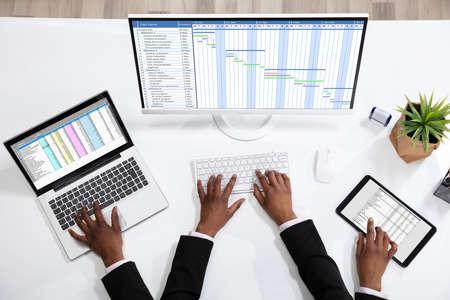 Une vue aérienne d'un homme d'affaires faisant du travail multitâche sur le lieu de travail