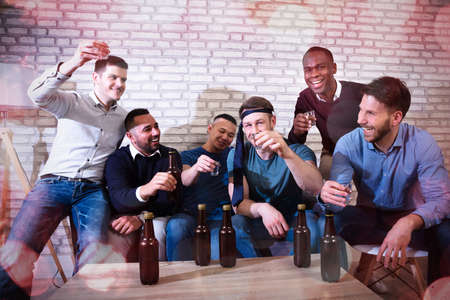 Group Of Cheerful Young Men Toasting With Tequila At A Nightclub Stockfoto - 124797888