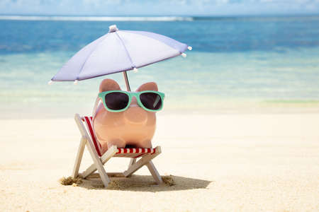 Pink Piggybank With Sunglasses And Umbrella On Deck Chair On Sand At Beach Stockfoto