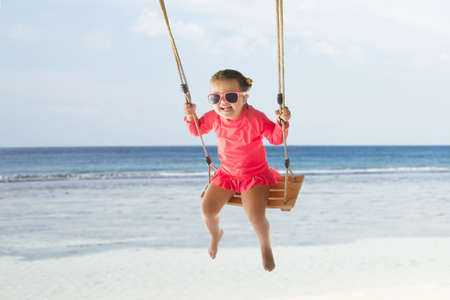 Portrait Of A Happy Toddler Girl Swinging On Beach Under The Tree