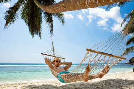 Close-up Of A Young Man Relaxing On Hammock Tied On Palm Tree On Beach Stockfoto