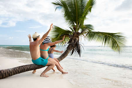 Family Sitting Together On Crooked Palm Tree Trunk Enjoying Together On Sand At Beach