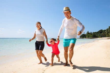Close-up Of Happy Toddler Girl Running With Their Parents On Sand At Beach Stock Photo