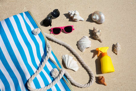Seashells, Sunglasses, Sunscreen Bottle And Handbag On Sand At Beach