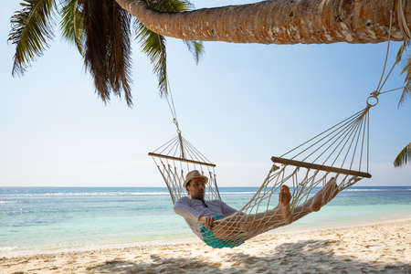 Young Man Sleeping On Hammock Under The Coconut Tree On Sand At Beach Stockfoto