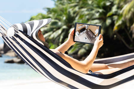 Woman Lying On Hammock Monitoring Cameras Live View On The Digital Tablet At Beach Stockfoto