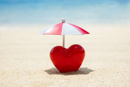 Close-up Of Red Painted Heart Under The Umbrella On Sand At Beach