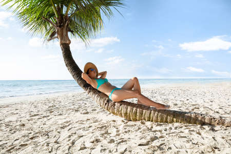 Young Woman In Bikini Relaxing On Crooked Palm Tree At Sandy Beach