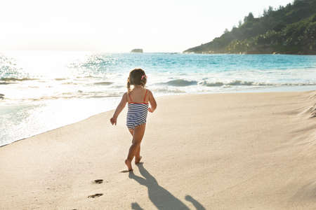 Rear View Of A Toddler Girl In Swimsuit Walking In Sand At Beach Stockfoto - 124798321