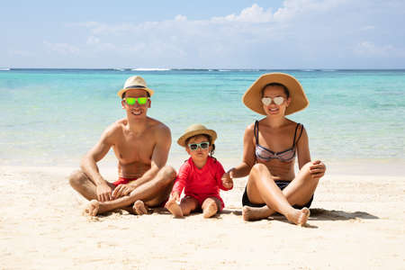 Portrait Of A Happy Family Wearing Sunglasses Sitting On Sand At Beach Stockfoto