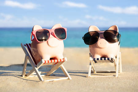 Close-up Of Two Piggybanks With Sunglasses On Deck Chairs Enjoying The Holiday At Beach
