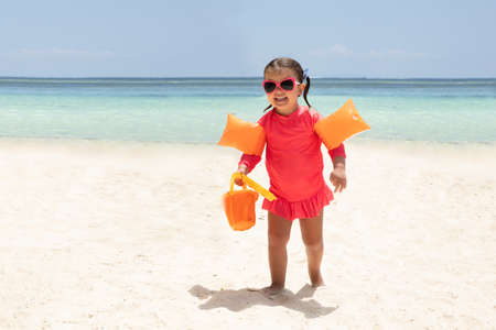 Portrait Of A Happy Toddler Girl Holding Plastic Toys In Hand Walking On Sandy Beach