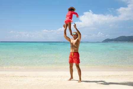 Father Wearing Sunglasses And Hat Throwing His Young Daughter In The Air At Beach Stockfoto