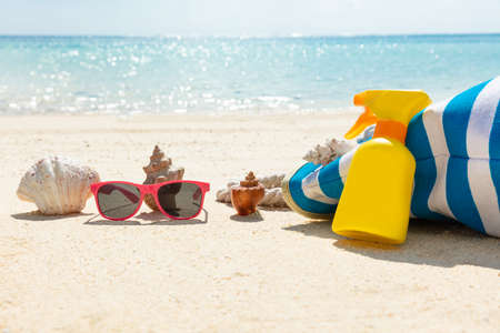 Sunglasses, Seashell, Sunscreen Lotion And Handbag On Beach