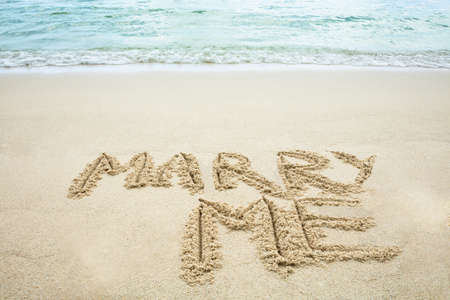 Marry Me Written On Sand With Footprints Near The Sea At Beach Stockfoto - 124798423